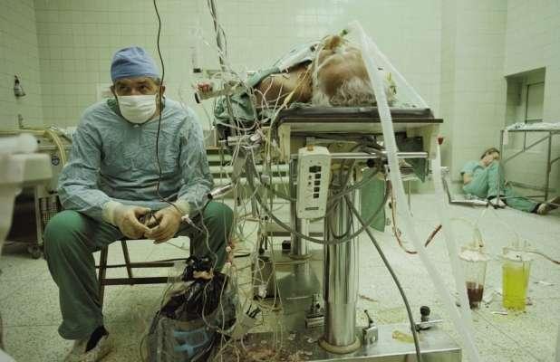 Il dott. Religa monitora i segni vitali di un suo paziente dopo un intervento chirurgico di trapianto di cuore durato 23 ore. Il suo assistente dorme in un angolo. [1987]