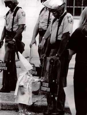 Il figlio di un membro del Ku Klux Klan tocca il proprio riflesso sullo scudo antisommossa di un poliziotto Afroamericano durante una dimostrazione. [1992]