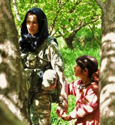 Una ragazzina Afgana incuriosita tiene la mano ad una soldatessa Americana