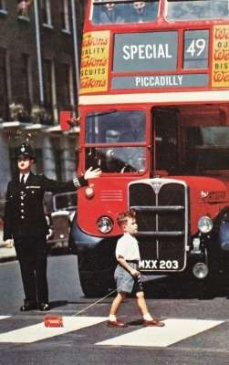 Un bambino attraversa una strada di Londra trascinandosi un autobus a due piani giocattolo.