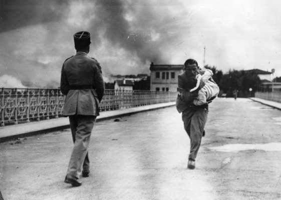 Un giornalista attraversa di corsa un ponte per salvare un neonato durante la Guerra civile [1936]