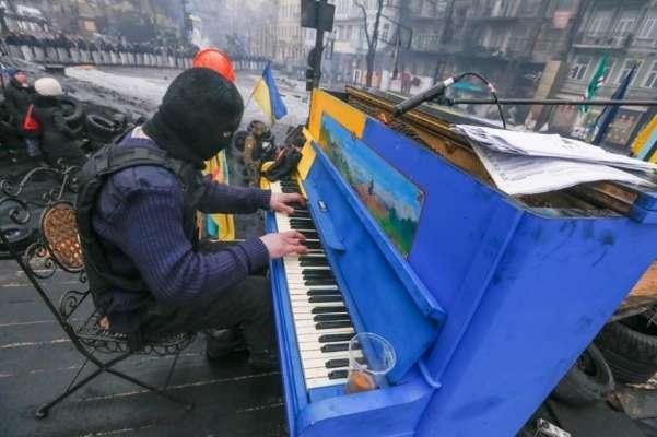 Dissidente suona il pianoforte nel caos con la polizia in tenuta antisommossa nello sfondo.